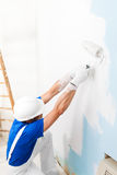 Pintor que pinta una pared con el rodillo de pintura Imagenes de archivo