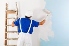 Pintor que pinta una pared con el rodillo de pintura Imagen de archivo libre de regalías