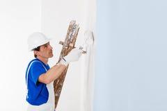 Pintor que pinta una pared con el rodillo de pintura Imagen de archivo