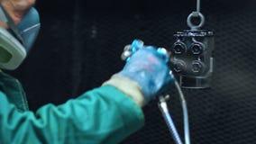 Pintor que pulveriza a cor preta nas peças da máquina na planta industrial video estoque