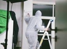 Pintor que trabaja con el rodillo y los cepillos de pintura para pintar el cuarto Imagen de archivo