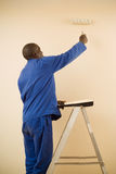 Pintor que usa um rolo de pintura Fotos de Stock Royalty Free
