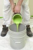 Pintor que vierte la pintura verde Fotos de archivo libres de regalías