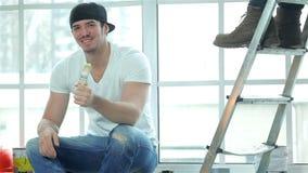 Pintor sonriente del trabajador que se sienta en una ventana almacen de video