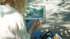 Pintor talentoso que trabaja al aire libre con la acuarela metrajes