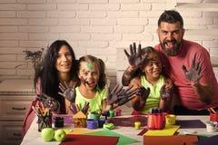 Pintores de las muchachas que pintan con la madre y el padre fotos de archivo libres de regalías