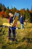 Pintores jovenes en el trabajo cerca de la cascada Fotos de archivo