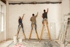 Pintores que trabalham no local da renovação fotografia de stock royalty free