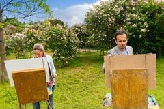 Pintores serios del hombre y de la mujer que pintan en el aire abierto Imagenes de archivo