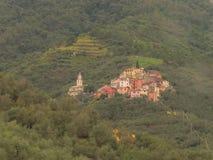 Pintoresco poca ciudad en un fondo verde borroso Localizado en las colinas, cerca de Cinque Terra National Park foto de archivo