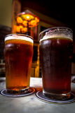 Pints of beer. Two pints of beer in a cozy pub Royalty Free Stock Image