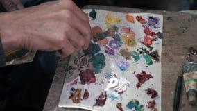 A pintura a óleo da cor da mistura da escova do artista na paleta está realizando em seu close up da mão filme