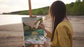 Pintura a óleo na praia Mulher que tira a imagem na armação video estoque