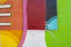 Pintura abstrata, colorida em uma parede de tijolo Imagens de Stock