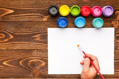 Pintura acrílica, folha branca e mão em um fundo de madeira Foto de Stock