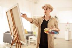 Pintura adolescente del pintor en una lona Foto de archivo