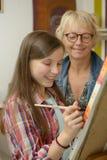 Pintura adolescente joven de la muchacha con su profesor Imagen de archivo libre de regalías