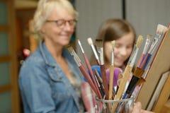 Pintura adolescente joven de la muchacha con su profesor Imágenes de archivo libres de regalías