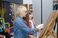 Pintura adolescente joven de la muchacha con su profesor Fotografía de archivo libre de regalías
