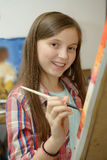 Pintura adolescente joven sonriente una lona Imagen de archivo
