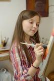 Pintura adolescente joven sonriente una lona Fotografía de archivo