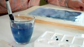 Pintura adulta del hombre con las pinturas coloreadas de la acuarela en un cierre casero del estudio para arriba