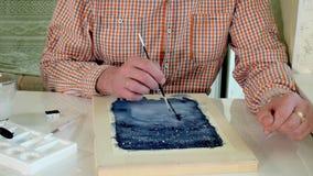 Pintura adulta del hombre con las pinturas coloreadas de la acuarela en un estudio casero