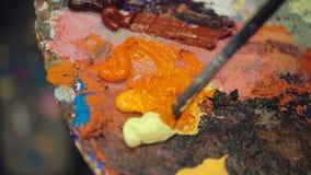 Pintura al óleo del color de la mezcla del cepillo del artista en la paleta almacen de metraje de vídeo
