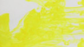 Pintura amarilla de las gotitas en agua en un fondo blanco almacen de metraje de vídeo