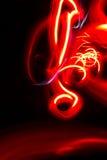 Pintura anaranjada roja abstracta de la luz del adorno en fondo negro Foto de archivo