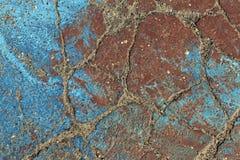 Pintura azul y marrón en el asfalto dañado Imagen de archivo libre de regalías