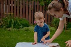 A pintura bonito do rapaz pequeno com uma pintura entrega usando pinturas desajeitados fotografia de stock