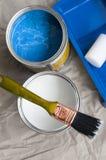 Pintura branca e azul em umas latas e em uma escova Imagens de Stock Royalty Free