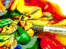 Pintura coloreada mezclada en la paleta Cepillo sucio en el primero plano Foto de archivo