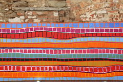 Pintura colorida de las tiras en una pared de piedra Foto de archivo