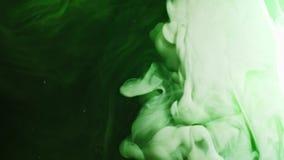 A pintura colorida do arco-íris deixa cair da parte inferior que mistura na água Close-up vídeos de arquivo