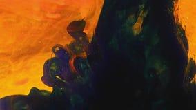 A pintura colorida do arco-íris deixa cair da parte inferior que mistura na água Close-up video estoque