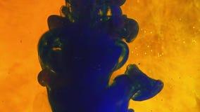 A pintura colorida do arco-íris deixa cair da parte inferior que mistura na água Close-up filme