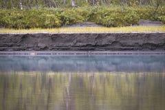Pintura como la reflexión en agua de río azul con la orilla del río texturizada hermosa Fotos de archivo libres de regalías