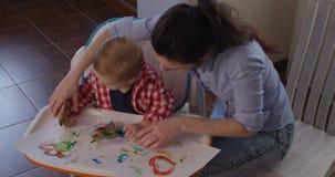 Pintura con las manos del niño femenino y pequeño metrajes