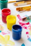 A pintura da pintura à têmpera de cores diferentes esverdeia escovas vermelhas amarelas azuis no fundo do Livro Branco com cursos imagens de stock