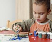 Pintura da criança com escova e cores Foto de Stock Royalty Free