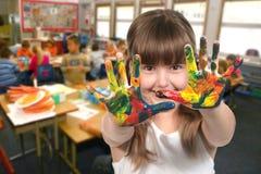 Pintura da criança de idade de escola com suas mãos na classe Fotografia de Stock Royalty Free