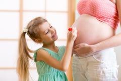 Pintura da filha da criança na barriga grávida da mãe foto de stock