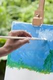 Pintura da jovem mulher no parque Imagens de Stock Royalty Free