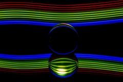 Pintura da luz da bola de vidro - listras vermelhas verdes azuis fotografia de stock