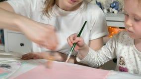 Pintura da mãe e da criança com dedos coloridos Os jogos com crianças afetam o desenvolvimento de crianças adiantadas video estoque