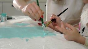 Pintura da mãe e da criança com escova colorida Os jogos com crianças afetam o desenvolvimento de crianças adiantadas filme