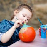 Pintura da menina da criança com cores na abóbora Foto de Stock Royalty Free