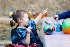 Pintura da menina da criança com cores na abóbora Imagem de Stock Royalty Free